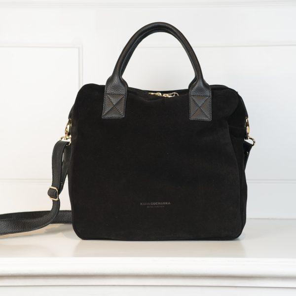 Tasche Eve ist in einer eher quadratischen Form gehalten und trägt die Farbe Schwarz. Der Reißverschluss, Das Logo und die Gurtschnallen sind in Gold