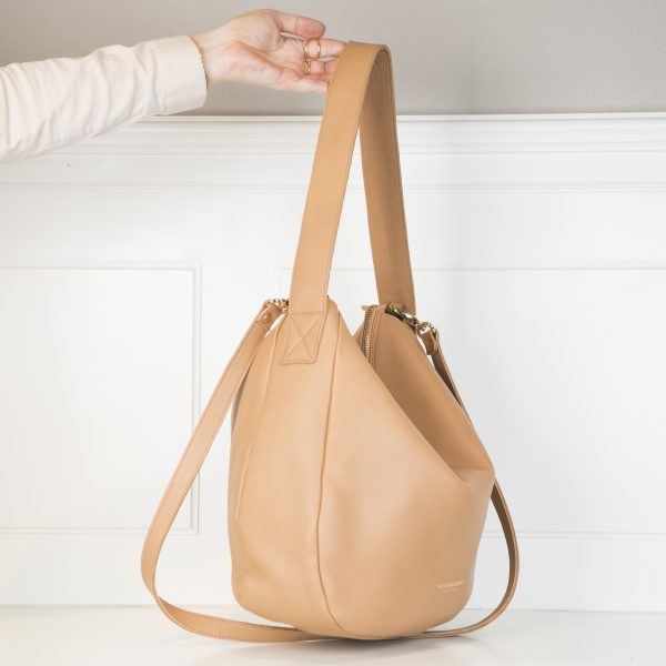 Die hellbraune Tasche Namens Sandle hat einen kürzeren Henken zum Tragen und einen längeren Henkel