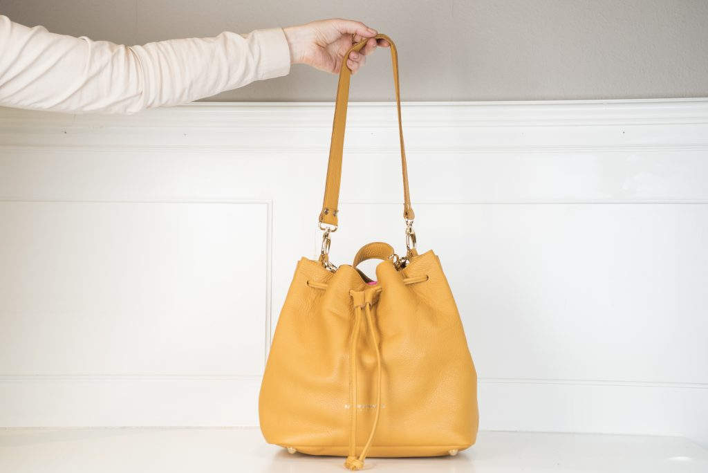 Die gelbe Beuteltasche Namens Kiki, ist aus hochwertigem Leder designt und schließt sich durch ein Lederband in der selben Farbe mit einem Tunnelzug.