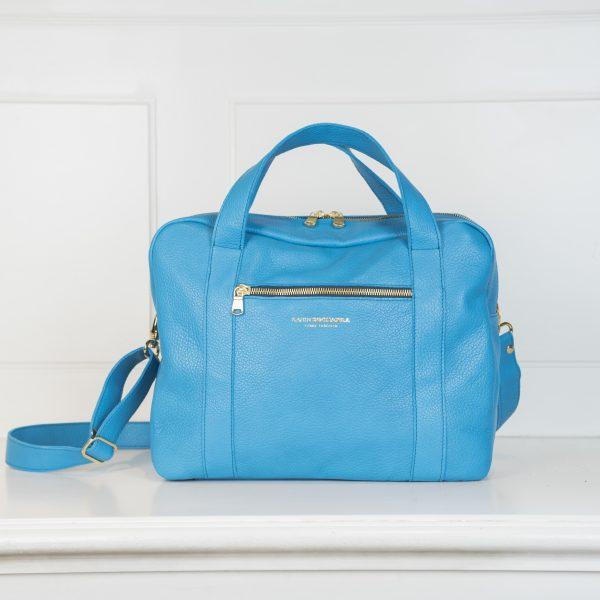 Die Tasche Business Klein ist in einem neonblau gehalten und hat auf der Vorderseite eine weiter Tasche mit Reißverschluss in Gold
