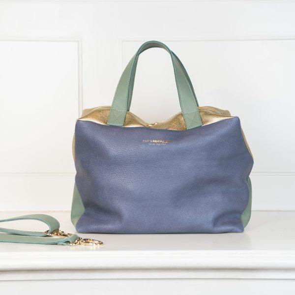 Die Tasche X4 ist mit drei Farben bestückt. Die Vorderseite besteht aus einem Blauton, die Hänkel und der Tragegurt aus einem Grün und die Oberseite der Tasche , so wie das Logo und die Schnallen sind in gold gehalten