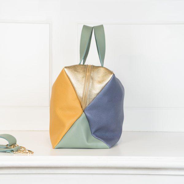 Die Tasche X4 ist mit vier verschiedenen Farben bearbeitet. Die Vorderseite der Tasche hat einen Blauton , die Rückseite trägt die Farbe gelb und die Unterseite, so wie die Hänkel und der Tragegurt sind in Grün gehalten und die Oberseite der Tasche is in einem metallic gold