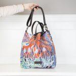 Die Tasche Linda ist mit einem bunten floralen Phantasiemuster versehen und hat zwei unterschiedliche Henkel aus dunklem Leder. Den einen längeren Henkel.