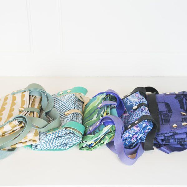 Hier sieht man die Falttaschen Baginbag in den verschiedenen Designs aufgereiht. Es ist eine Tasche mit mintgrünen Händeln zu sehen, die ein Musterdruck in den Farben weiß und gold hat , dann eine Tasche mit grünen Händeln und Türkies/ weißem Muster, eine Tasche mit Blau/Lila Händeln und einem Dschungelfarbigen Muster, eine Tasche mit schwarzen Händeln und einem Blau/weiß/ rosa Blumenmuster und eine Tasche in Lila mit schwarzem Aufdruck