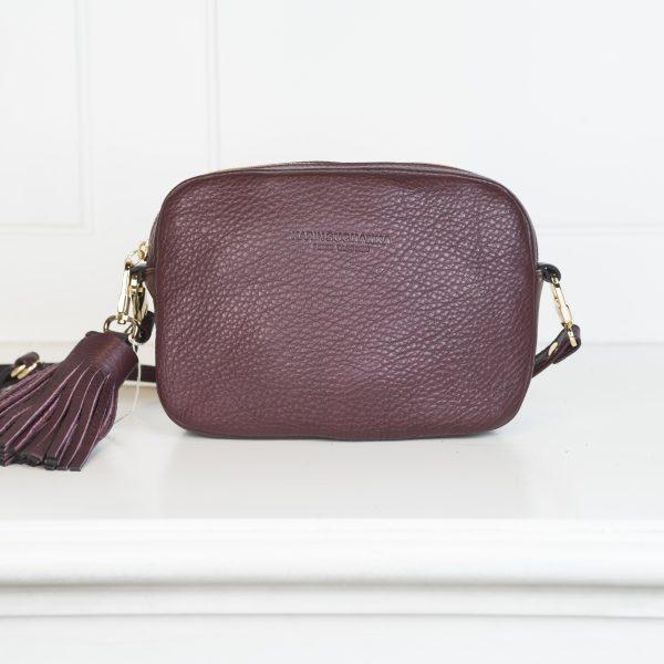 Die Crossbody Lilly – Tasche ist in Aubergine gehalten und ist mit einem Anhänger aus dem selben Ledermaterial wie die Tasche besetzt. Reißverschluss ist in Gold