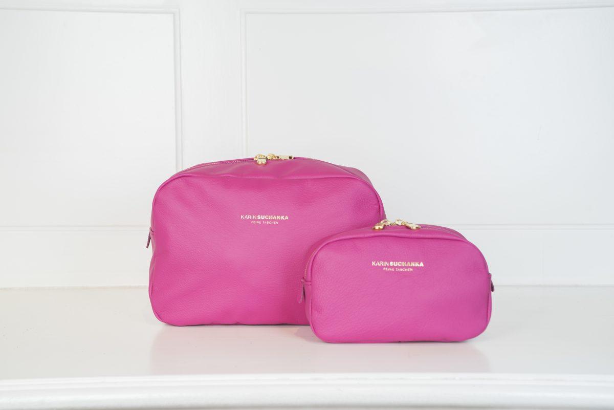 Es sind zwei Schminktäschchen in pink angezeigt, die in zwei verschiedenen Größen abgebildet sind. Das Logo und die Reißverschlussschnalle sind in gold