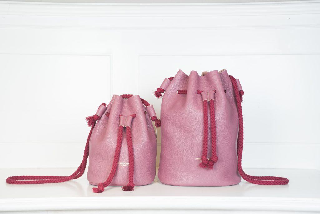 Umhängetaschen Fastly und Fast in Beutelform. Die Taschen sind in der Farbe Himbeere zu sehen und werden durch eine rote Korden geschlossen und auch der Tragegurt besteht aus der selben Kordel und Farbe