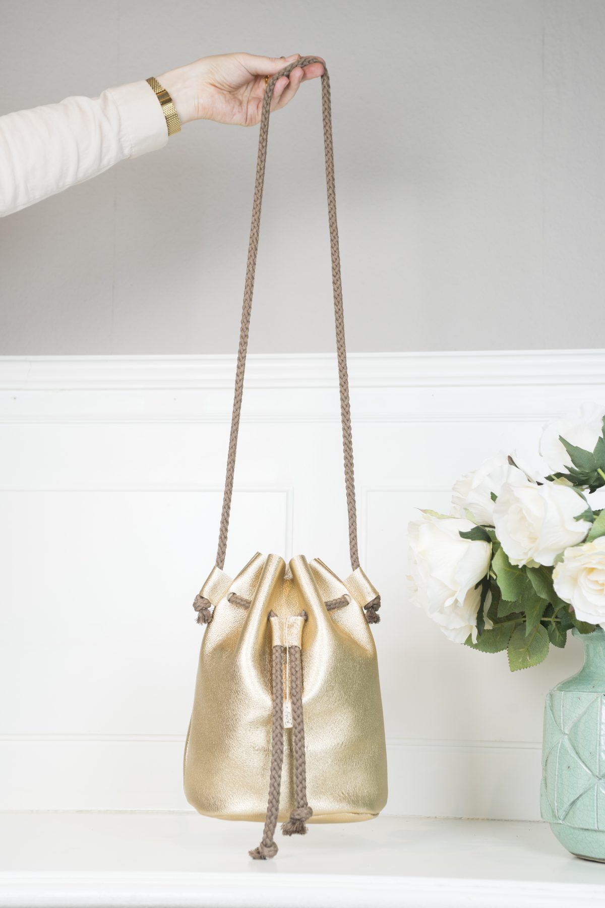 Die Beuteltasche Fastly ist in metallic gold gehalten und besitzt eine Kordel aus Naturfarben zum Schließen und Umhängen