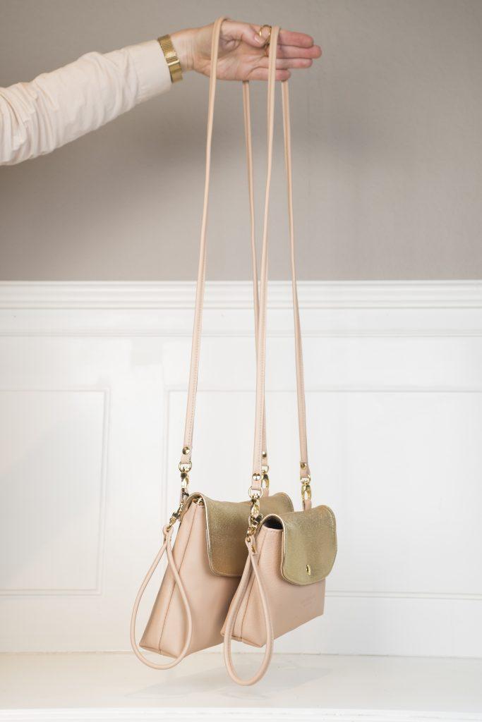 Die Clutch, Crossbody Lou & Loulu – nude /metallic gold hängen an einem Arm und sind in zwei verschiedenen Größen angezeigt.Schnallen und Druckknopf sind in gold gehalten
