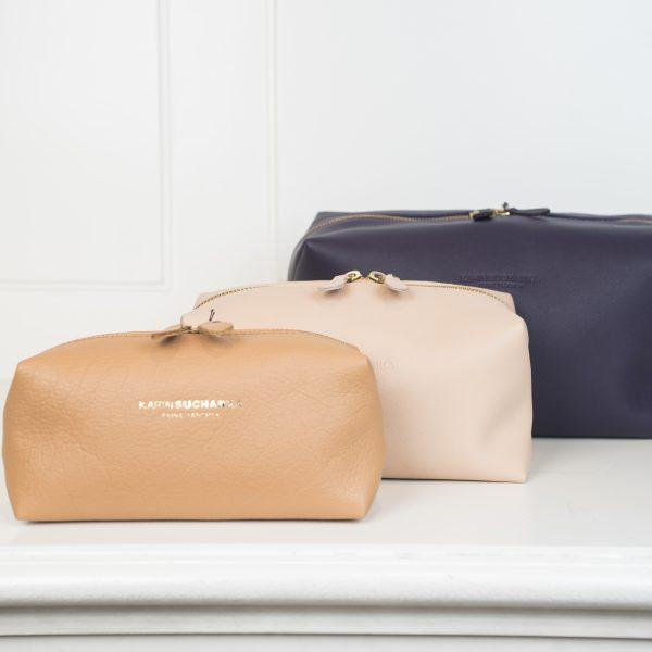 Die Kulturbeutel und Schminktäschchen sind in 3 Farben und Größen angezeigt. Die vordere Tasche ist in hellbraun gehalten, die mittlere in beige und die hintere Tasche in dunkelblau. Alle drei Taschen werden mit einem Reißverschluss verschlossen.