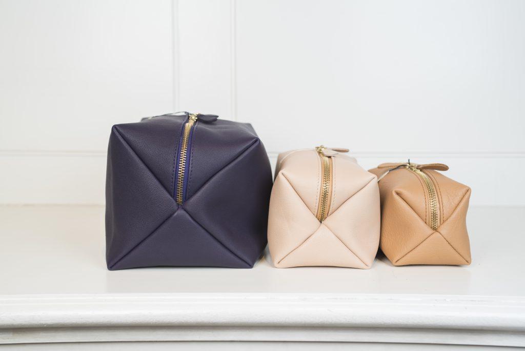 Die Kulturbeutel und Schminktäschchen sind in 3 Farben und Größen angezeigt und von der Seite sichtbar. Die vordere Tasche ist in hellbraun gehalten, die mittlere in beige und die hintere Tasche in dunkelblau. Alle drei Taschen werden mit einem Reißverschluss verschlossen.