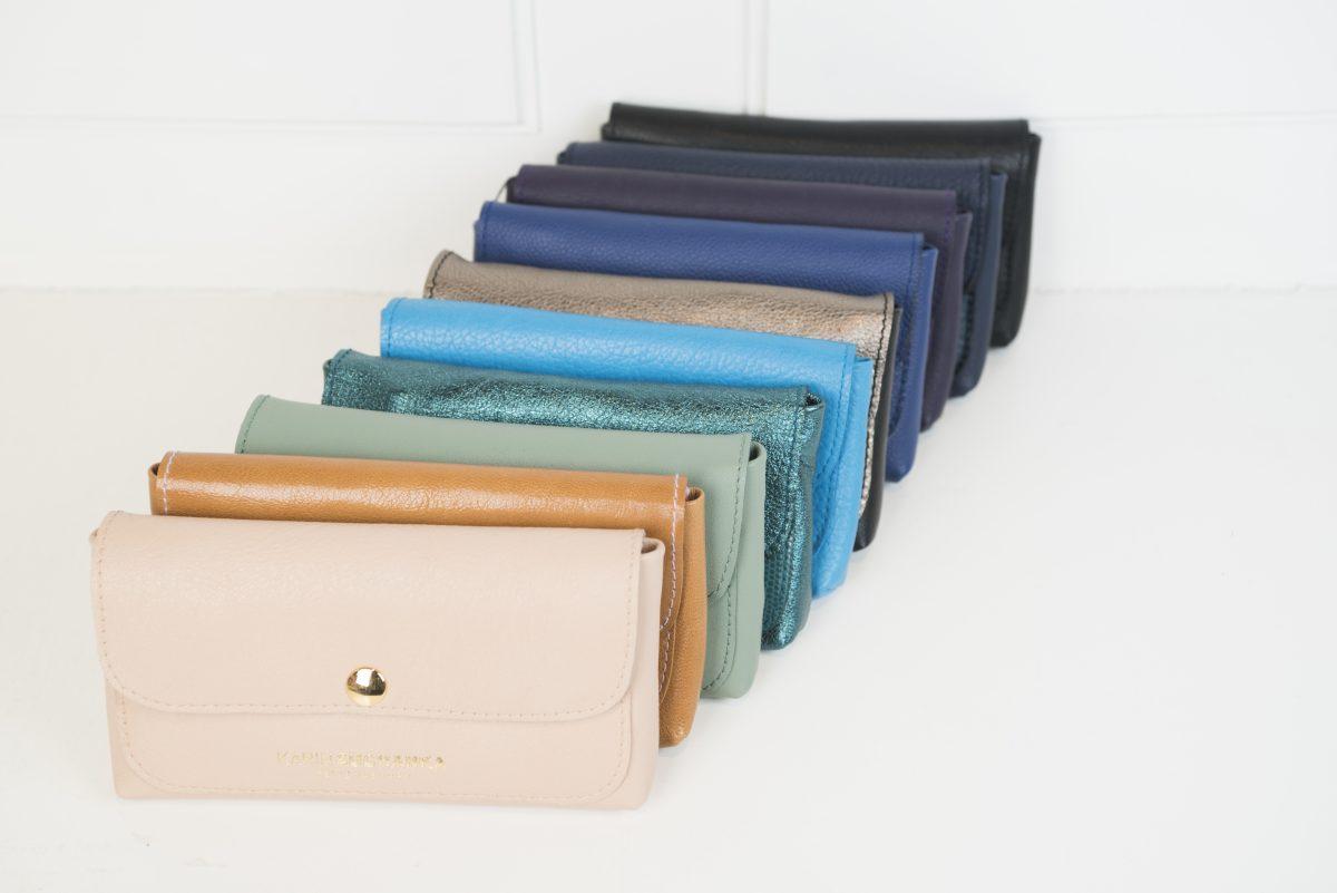 Die Geldbörsen Dodo sind in verschiedenen Farben aufgereiht. Aufgezeigt sind die Farben beige, braun, grün, glänzendes Tannengrün, neon blau, gold, Koboldblau, lila, dunkelblau, schwarz