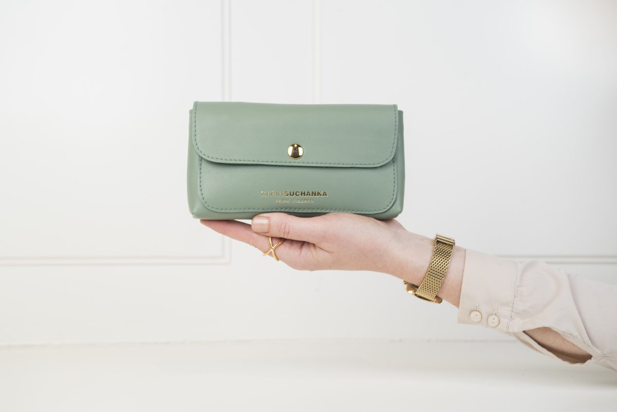 Geldbörse in Grün liegt auf der Hand und ist handgroß. Sie hat einen goldenen Duckknopf und vergoldeten Logo