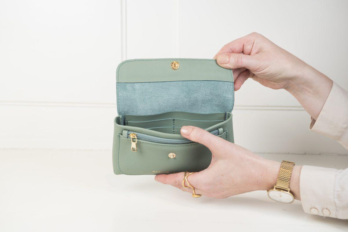 Die Geldbörse Dodo in grün beinhaltet einige Fächer und hat eine Außentasche mit Reißverschluss. Die Details wie Druckknopf, Logo und Reißverschlussgriff sind in gold gehalten