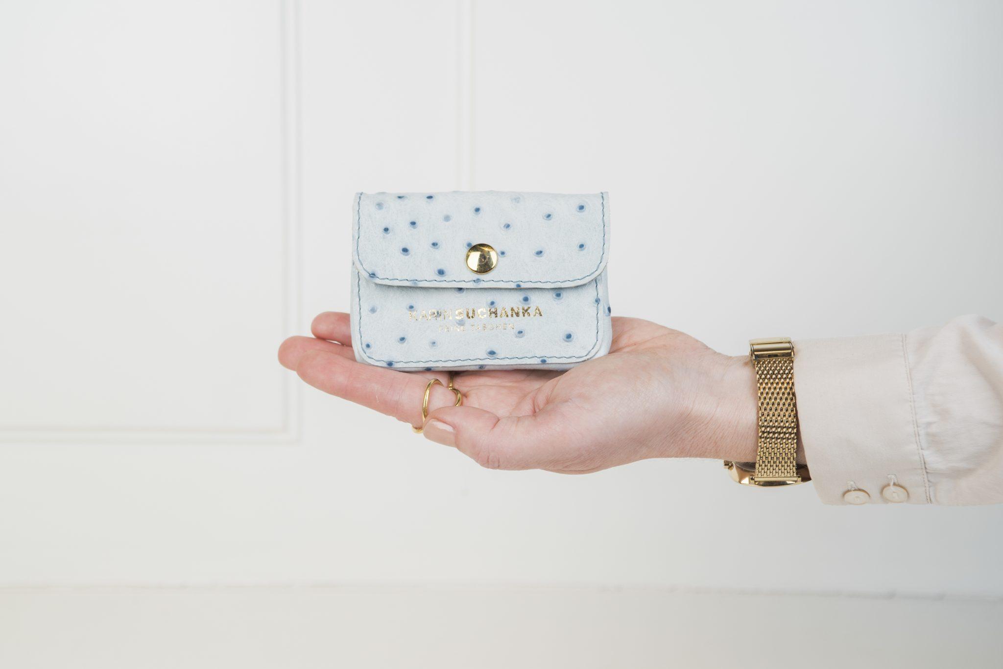 Minibörse in hellblauen, gepunktetem Leder liegt auf einer Hand. Details wie Druckknopf und Logo sind in Gold gehalten