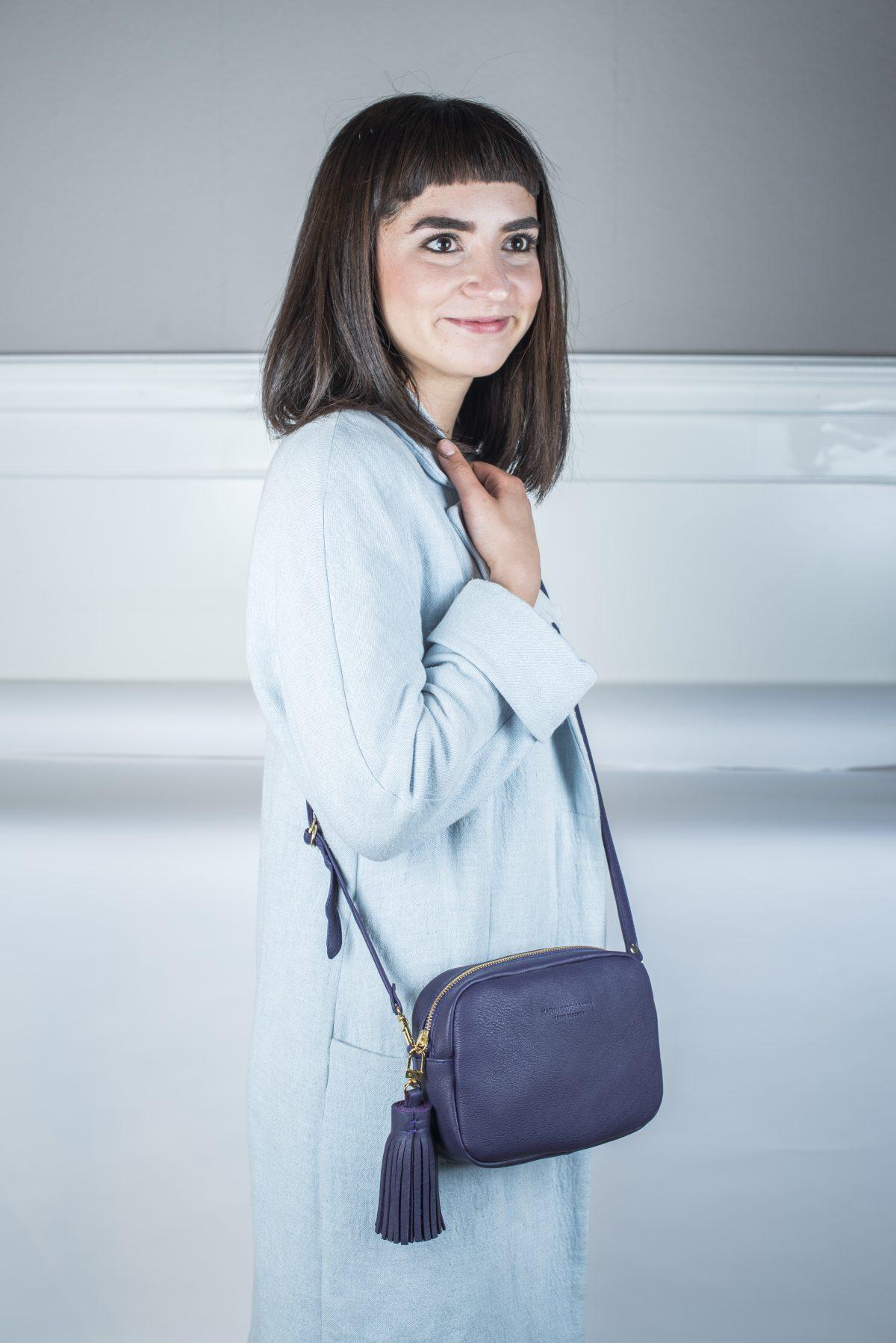 Die Crossbody Lilly – Tasche ist in Lila gehalten und ist mit einem Anhänger aus dem selben Ledermaterial wie die Tasche besetzt. Reißverschluss ist in Gold