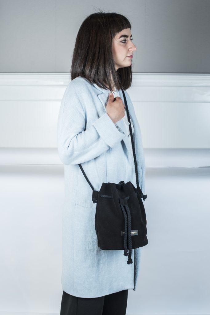 Frau trägt Umhängetasche Fastly in Beutelform. Die Tasche ist in schwarz zu sehen und wird durch eine schwarze Kordel geschlossen und auch der Tragegurt besteht aus der selben Kordel und Farbe