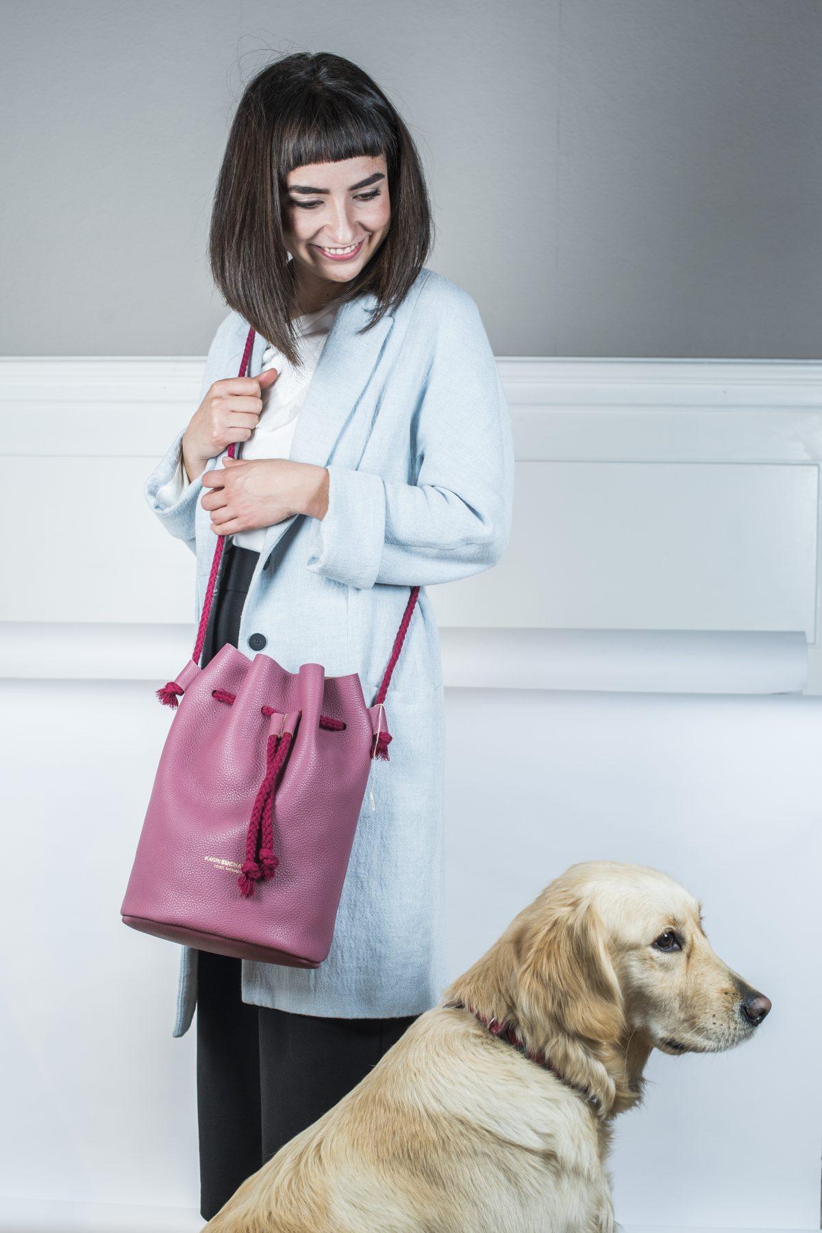Frau mit Hund trägt eine Umhängetasche in Beutelform. Die Tasche hat die Farbe Himbeere und wird durch eine rote Korden geschlossen und auch der Tragegurt besteht aus dem selben Kordel