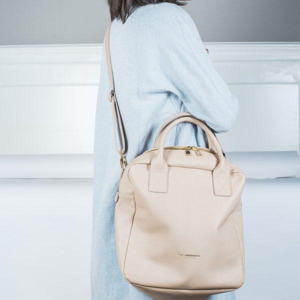 Frau trägt die Tasche Boy von Karin Suchanka umgehängt in creme Farben. Das logo, der Reißverschluss und die Gurtschnallen sind in Gold gehalten