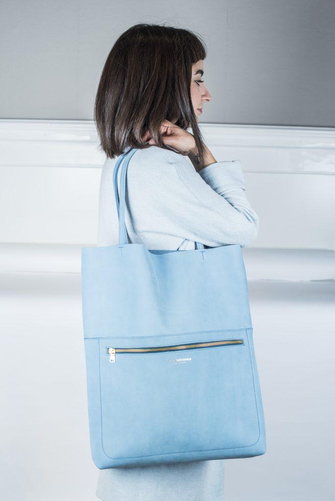 Frau trägt eine große hellblaue Tasche. An der Vorderseite befindet sich noch ein Steckfach mit einem goldenen Reißverschluss versehen