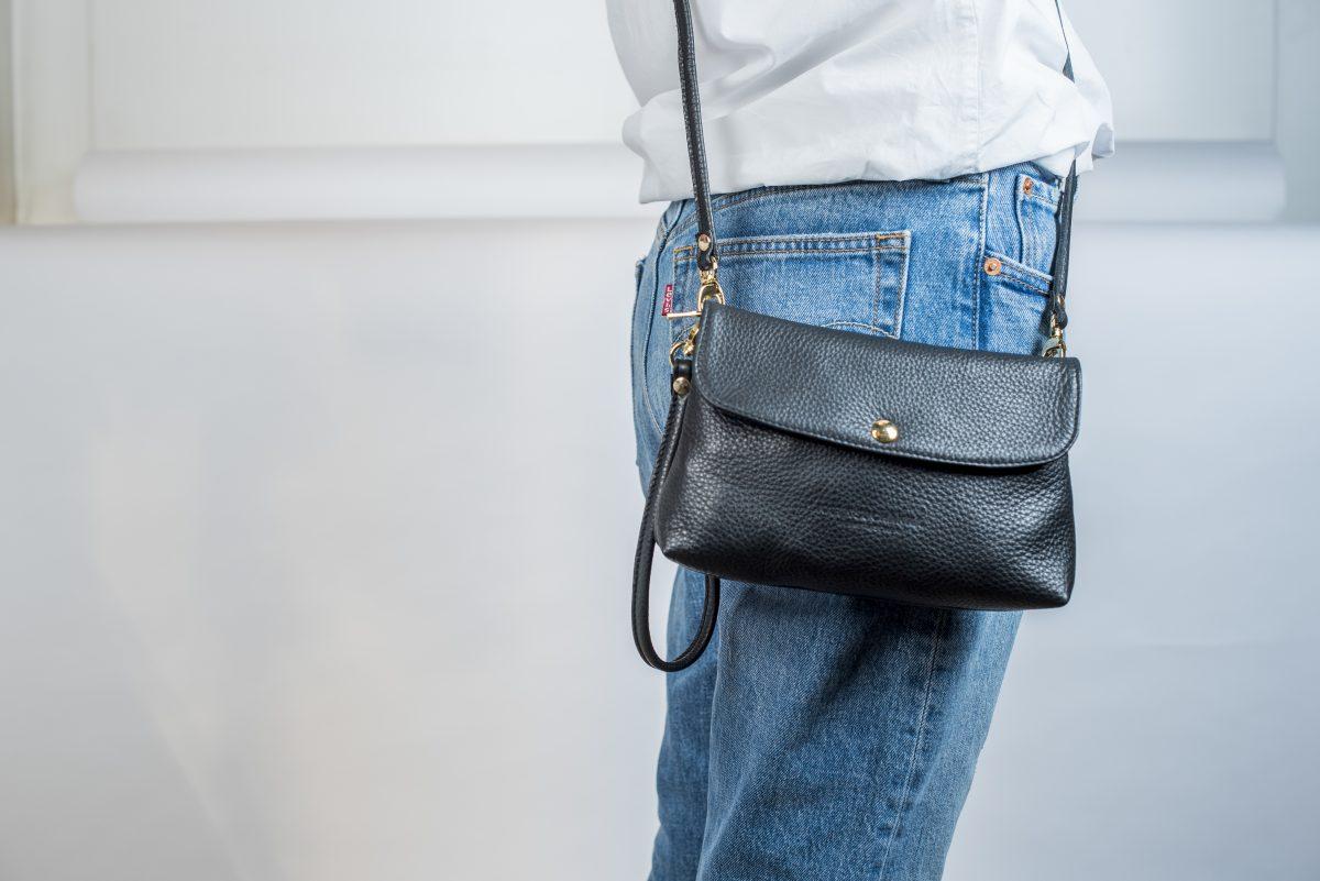 Man sieht ein Seitenansicht von Jemanden der die Crossbody - Tasche Lou über den Schultern trägt . Die Tasche ist im schwarzen Leder gehalten, hat eine Clutch- Schlaufe angebracht und die Details wie Druckknopf vorne und die Schnallen sind in gold